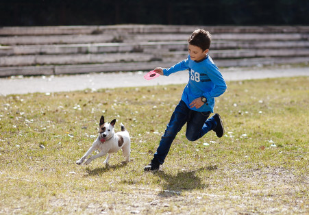 Dog_Dog-Running-With-Boy_shutterstock_248645074-451x314